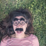 girl with groucho glasses in grass
